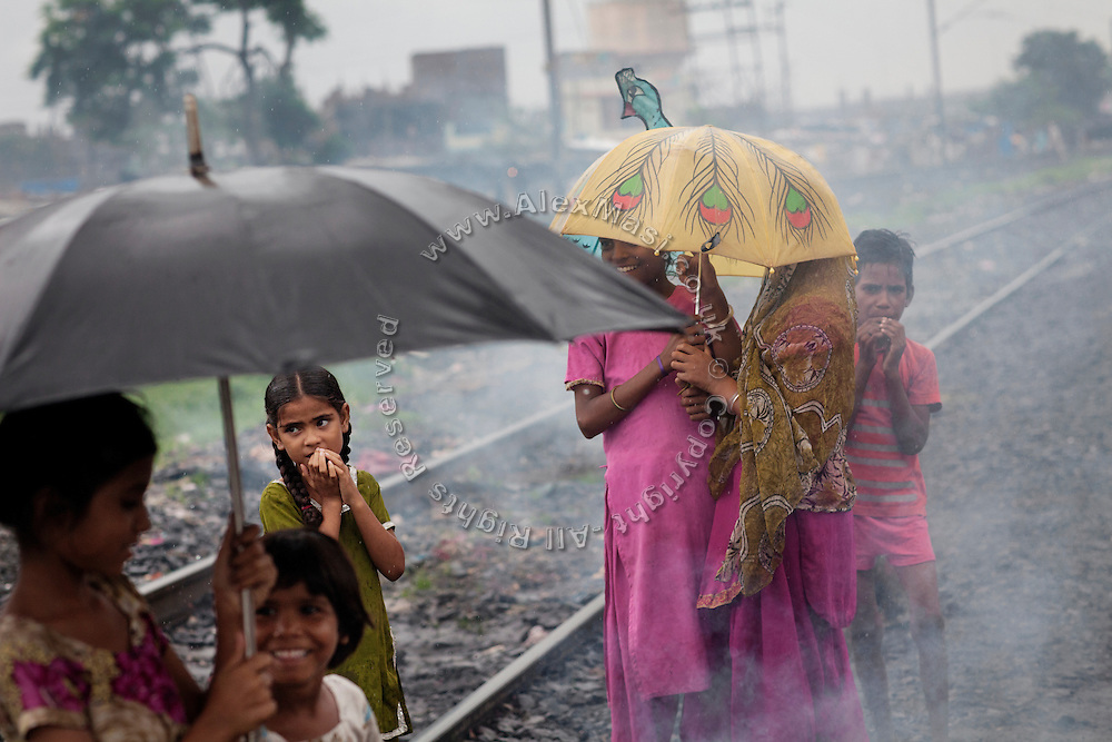 Children are standing along the railway tracks passing through New Arif Nagar, one of the water-affected colonies surrounding the abandoned Union Carbide (now DOW Chemical) industrial complex in Bhopal, Madhya Pradesh, India. The poisonous cloud that enveloped Bhopal left everlasting consequences that today continue to consume people's lives.