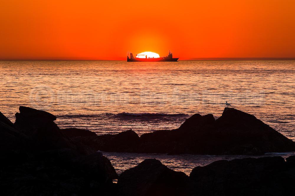 Vessel passing by the sun at sunset   Båt som passerer solen ved solnedgang