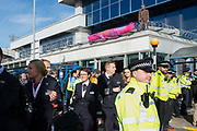 Flight attendents walk by as a Extinction Rebellion protester stands on a roof at London City Airport during day four of two weeks of planned demonstrations on 10th October, 2019 in London, Untited Kingdom. Extinction Rebellion is demanding that governments drastically cut carbon emissions.