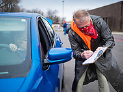 06 APRIL 2020 - DES MOINES, IOWA: RICHARD JESS, a volunteer, checks in a family picking up a box of food during a drive through emergency food distribution at First DSM Church in Des Moines. On Monday, 06 April, Iowa reported 946 confirmed cases of the Novel Coronavirus (SARS-CoV-2) and COVID-19. There have been 25 deaths attributed to COVID-19 in Iowa. Most non-essential businesses are closed until 30 April. Well over 100,000 Iowans filed first time claims for unemployment in the last three weeks, more than applied during the peak of the Great Recession of 2008. Local food banks have seen an equal spike in people seeking nutritional assistance. First DSM Church has increased their food pantry from one day weekly to three days per week. Hundreds of people lined up Monday to get a box of food and one roll of toilet paper at the church's drive through pantry.          PHOTO BY JACK KURTZ