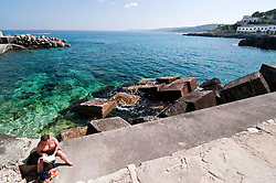 Castro Marina - Salento - Puglia - Porto di Castro Marina. Una bagnante si gode il primo sole della stagione balneare.