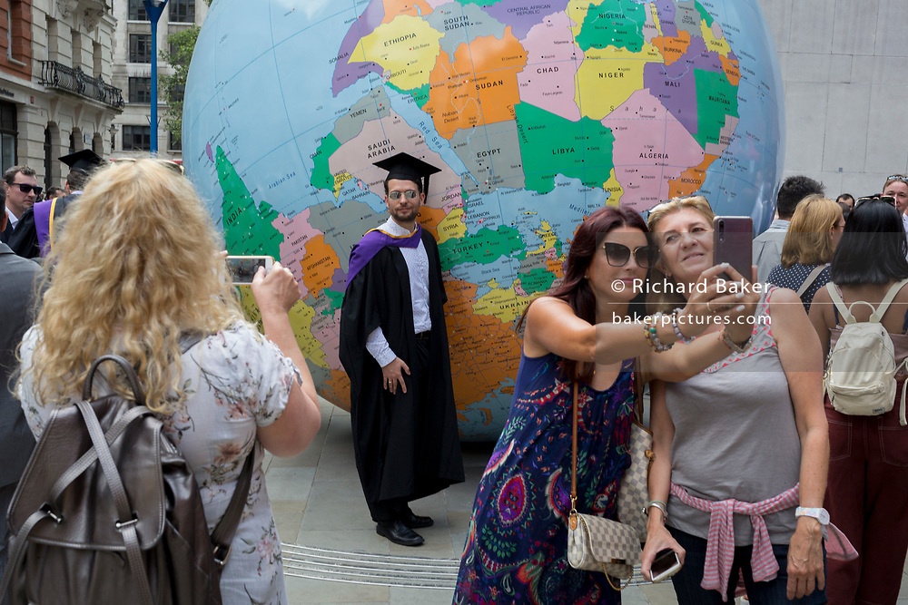 "Beneath the sculpture by Turner Prize-winning artist Mark Wallinger entitled ""The World Turned Upside Down', new graduates straight after their graduation ceremonies meet family and friends outside the London School of Economics (LSE), on 22nd July 2019, in London, England. 'The World Turned Upside Down' is a large political globe, four metres in diameter, with nation states and borders outlined but with the simple and revolutionary twist of being inverted. Most of the landmasses now lie in the 'bottom' hemisphere with the countries and cities re-labelled for this new orientation."