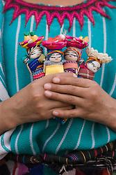 Child holding small handmade dolls in her hands, Chichicastenango, Guatemala
