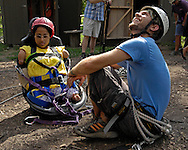 Directv Magazine -- Minda Cox (R) waits to be lifted up to the zip line with Camp Barnabas counselor Kevin.
