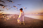 A young boy wrapped in a towel walks down a beach with seagulls chasing after him