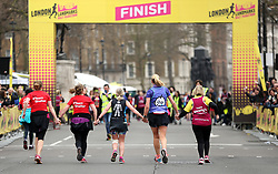 Runners hold hands on the way to the finish line of the 2018 London Landmarks Half Marathon. PRESS ASSOCIATION Photo. Picture date: Sunday March 25, 2018. Photo credit should read: Steven Paston/PA Wire