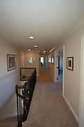 View of main second floor hallway from seating area.  On right is media room and on left at midway down the hall is a bathroom (with walk in shower) that also connects to room above garage (shown as exercise room).