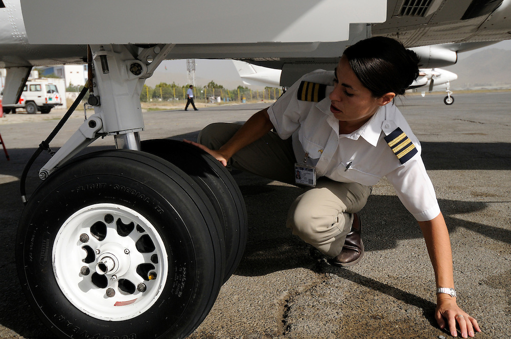 """Pilot, Danielle Aitchison, inspects the Beechcraft 1900D she flies in Afghanistan for The United Nations Humanitarian Air Service (UNHAS).    ...When asked about flying in a war zone, she says,  """"I'm just a normal average female.  My job is maybe a little different to some, but I have the same feminine side as other women.  I don't have any trouble going back to New Zealand relating to people.  I'm just a regular chick.""""."""