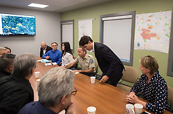 Prime Minister Justin Trudeau, centre right, takes a seat beside B.C. Fire Protection Officer Tom Reinboldt, back centre, for a meeting with officials during a visit to the Prince George Fire Centre, in Prince George, B.C., on Thursday August 23, 2018. Photo by Darryl Dyck/CP/ABACAPRESS.COM