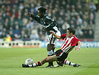 Photo. Andrew Unwin.<br /> Southampton v Newcastle United, FA Cup Third Round, Friends Provident St Marys Stadium, Southampton 03/01/2004.<br /> Southampton's Paul Telfer (r) puts in a sliding challenge on Newcastle's Olivier Bernard (l).