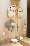 Standard generic bathroom fixtures reflected in a Paris hotel room mirror.