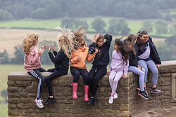 Licensed to London News Pictures. 30/07/2021.Dorking, UK. Kids from the Myti youth club in Tadworth, Surrey enjoy the views on top of Box Hill in Surrey despite the unseasonal stormy conditions today. Storm Evert hit the South Coast of England this morning with winds speed in excess of 65mph as the Met Office issue weather warnings for high winds, coastal gales and heavy rain with disruption to travel. Photo credit: Alex Lentati/LNP