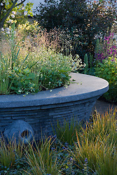Circular raised bed and stone seat. Planting  includes Briza media and Libertia peregrinans. Design: Cleve West, Bupa Garden, Chelsea 2008