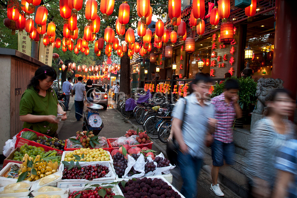 "A fruit seller plies her trade as red lanterns hang overhead along Guijie food street, the famous eating street in Beijing, China. known to locals as 'Ghost Street' as it remains open 24 hours a day, eating on Ghost Street is about more than food and drink, it's a way of life for many Beijingers. Tucked behind Dongzhimen Street, ""Ghost Street"" stretches 1.5km and contains more than 150 shops, including 100 restaurants, making it one of the most unique streets in Beijing."