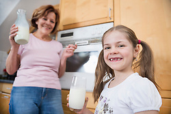 Grandmother and granddaughter holding glass of milk, smiling