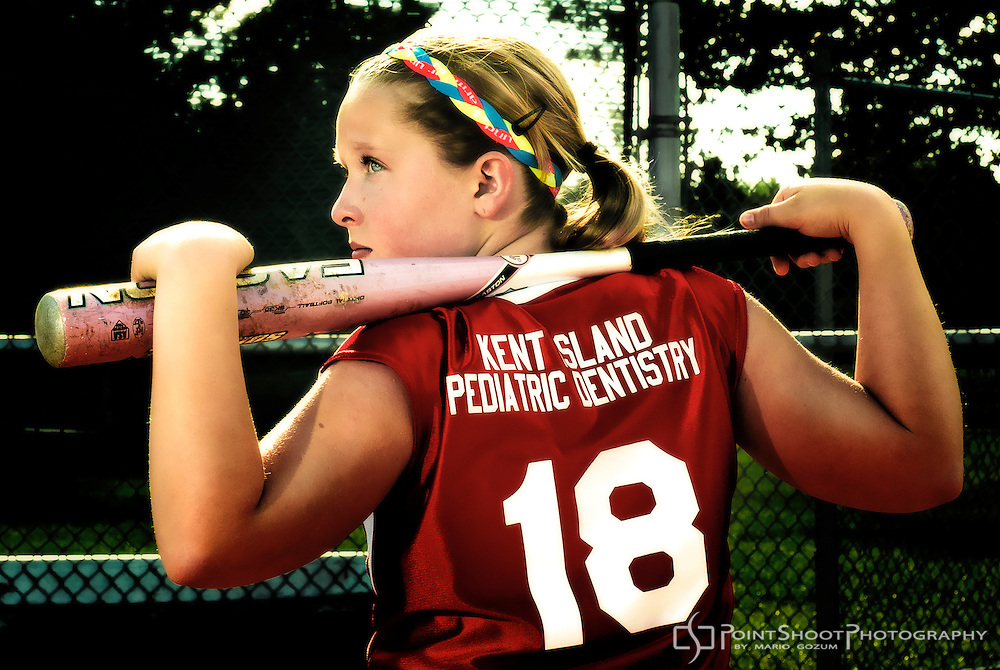 """Female Youth Softball Player. Rear profile, with bat resting across shoulders. """"18"""" and """"Kent Island Pediatric Dentistry"""" on jersey. By PointShoot Photography, Stevensville, MD"""