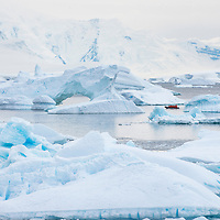 An inflatable boat (zodiac) filled with people takes a tour amidst icebergs in Port Charcot near Booth Island in Antarctica.