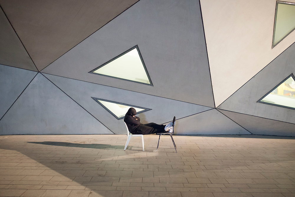 "A man is resting on two chairs, out the ""Tel-Aviv Museum of Art""."