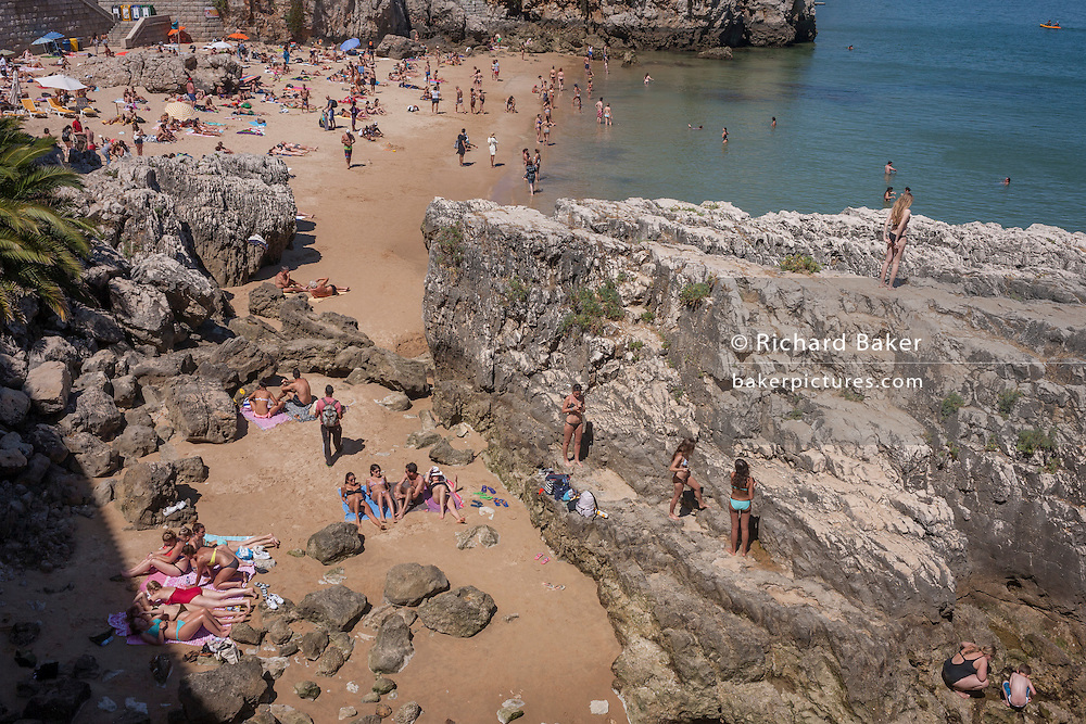 Sunbathers lie surrounded by rocks on the beach in mid-day heat, on 12th July 2016, at Cascais, near Lisbon, Portugal. Cascais is a coastal town and a municipality in Portugal, 30 kilometres (19 miles) west of Lisbon. The former fishing village gained fame as a resort for Portugal's royal family in the late 19th century and early 20th century. Nowadays, it is a popular vacation spot for both Portuguese and foreign tourists and located on the Estoril Coast also known as the Portuguese Riviera. (Photo by Richard Baker / In Pictures via Getty Images)