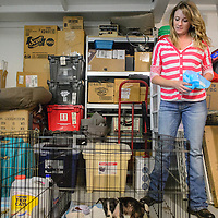 070915  Adron Gardner/Independent<br /> <br /> Kris Gruda cleans up the cage of Aero at her home in Gallup Thursday.  Aero is a foster puppy from the humane society who has mange.
