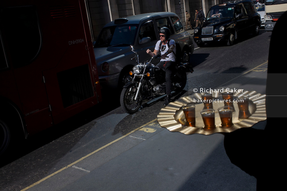 A biker on a motorbike waits in traffic in Threadneedle in the City of London, with a nearby shop employee offering passers-by samples of speciality tea.