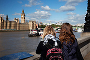 Tourists near the Houses of Parliament on the River Thames at Westminster, London. Also known as the Palace of Westminster, and the clock tower known as Big Ben.