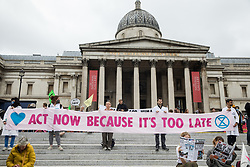 Environmental activists from Extinction Rebellion hold a banner in Trafalgar Square demanding urgent action on climate change during the first day of Impossible Rebellion protests on 23rd August 2021 in London, United Kingdom. Extinction Rebellion are calling on the UK government to cease all new fossil fuel investment with immediate effect in particular. (photo by Mark Kerrison/In Pictures via Getty Images)