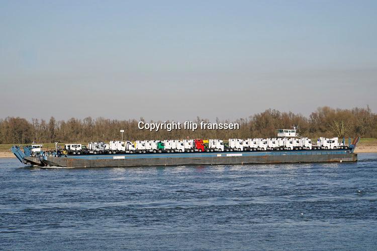 Nederland, Rijn, Waal, 27-2-2019Binnenvaartschip, autovervoer op de waal, rijn, richting Rotterdam. Vrachtwagens, trekkers staan op het dek van een rollonrolloff, roro, schip. De Waal is het Nederlandse deel van de Rijn en de belangrijkste vaarroute van en naar Rotterdam en Duitsland .Foto: Flip Franssen