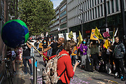An animal rights activist from Animal Rebellion strikes a pinata suspended from above a branch of Barclays Bank in Tottenham Court Road during a protest on 4 September 2020 in London, United Kingdom. Animal Rebellion were protesting against the provision by Barclays Bank of loans and underwriting to beef and dairy companies which are huge contributors to climate change.