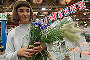 """""""New Covent Garden Wholesale Flower Market"""" (Photograph must be captioned like this - I had to sign a contract!!). <br /><br />Terri Chandler from Worm London selecting her flowers<br /><br />British flags and bunting adorn Pratley's market flower shop at New Covent Garden Wholesale Flower Market<br /><br />The main selling days for local British fresh flowers are on Monday and Thursday mornings. The main sellers are Pratleys<br /><br />British local flowers, grown nearby, count for around 10% of the UK market, traveling less than a tenth of their foreign counterparts which are often flown in from abroad. Nearly 90% of the flowers sold in the UK are actually imported, and many travel over 3000 miles. Local flower farms help biodiversity, providing food and habitat to a huge variety of wildlife, insects including butterflies, bugs, and bees. Often local flower farmers prefer to grow organic rather than using pesticides. British flowers bloom all the year around, even in the depths of winter, and there are local flower farms throughout the country.<br /><br />Many people like the idea of the just picked from the garden look, and come to flower farms throughout Britain to pick their own for weddings, parties and garden fetes. Others come for the joy of a day out in the countryside with their family. Often a bride and her family will come to pick the flowers for her own wedding, some even plant the seeds earlier in the year."""