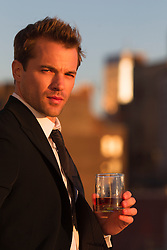 good looking man holding a drink at sunset