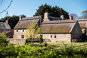 Hamptonne Country Life Musuem - a historic granite farmhouse with thatched roofs, surrounded by fields and grass in the countryside of Jersey, CI