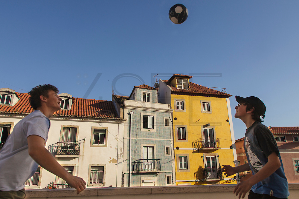 Boys playing football (soccer) at The National Pantheon, in Alfama, Lisbon, in front of ceramic-tiled and typical strong color painted facades.