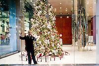 3 Dicembre 2008. New York, NY. Un impiegato conversa al cellulare nella hall di un palazzo sulla 6th avenue & 52nd street. Ogni anno le strade e i negozi di New York City sfoggiano decorazioni natalizie che attraggono turisti da tutto il mondo.<br /> ©2008 Gianni Cipriano per Io Donna / Corriere della Sera<br /> cell. +1 646 465 2168 (USA)<br /> cell. +1 328 567 7923 (Italy)<br /> gianni@giannicipriano.com<br /> www.giannicipriano.com