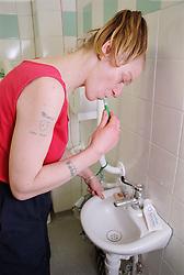 Female resident of homeless hostel brushing teeth at sink in shared bathroom,