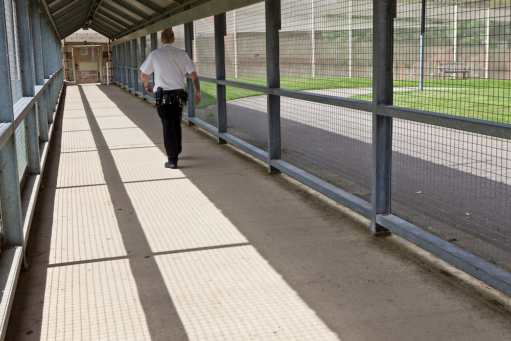A prison officer walks along one of the secure walkways linking some of the buildings. HMP The Mount, Bovingdon, Hertfordshire