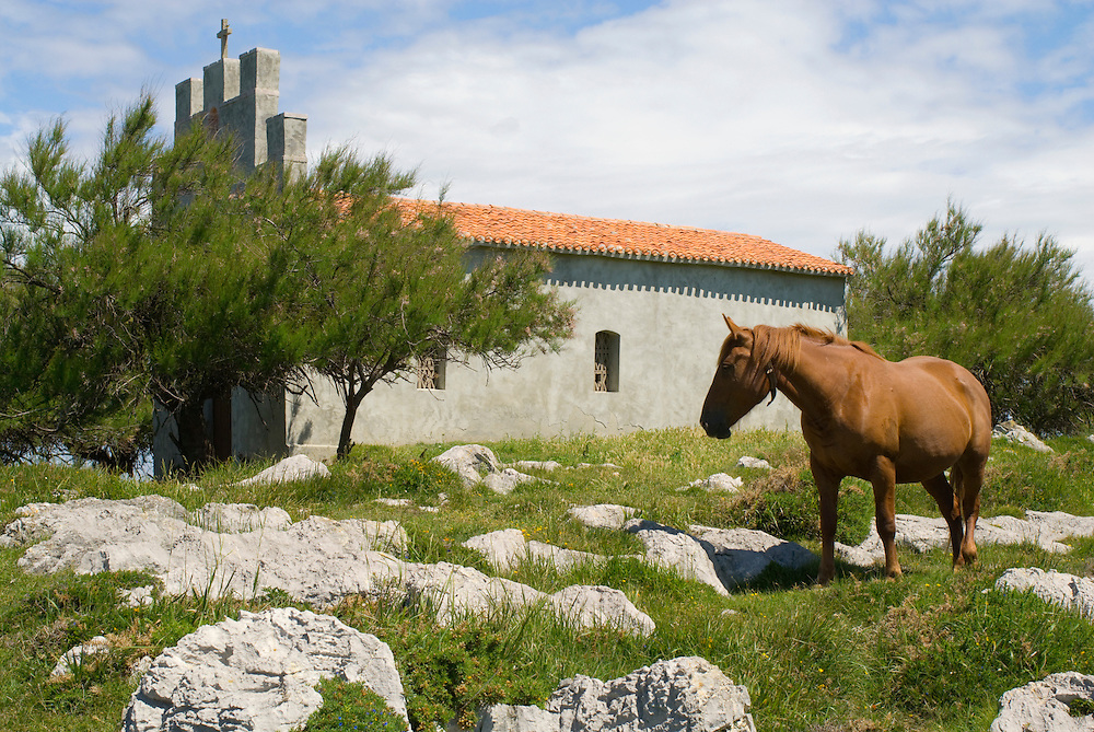 Church on the point overlooking Playa San Antonio, Asturias, Spain.
