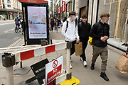 Young men out and about in the shopping district of Oxford Street, some wearing face masks and others not on 26th May 2021 in London, United Kingdom. As the coronavirus lockdown continues its process of easing restrictions, more and more people are coming to the West End as more retail businesses open.