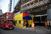 Colourful construction site hoarding on Bishopsgate creates a coincidence of colour in the City of London, England, United Kingdom. As Londons financial district grows in height, towers and skyscrapers take over.