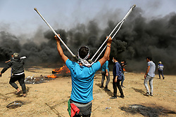 April 13, 2018 - Khan Younis, Gaza Strip, Palestinian Territory - Palestinian gather during clashes with Israeli security forces in a tent city protest where Palestinians demand the right to return to their homeland, at the Israel-Gaza border, in Khan Younis in the southern Gaza Strip.  (Credit Image: © Ashraf Amra/APA Images via ZUMA Wire)