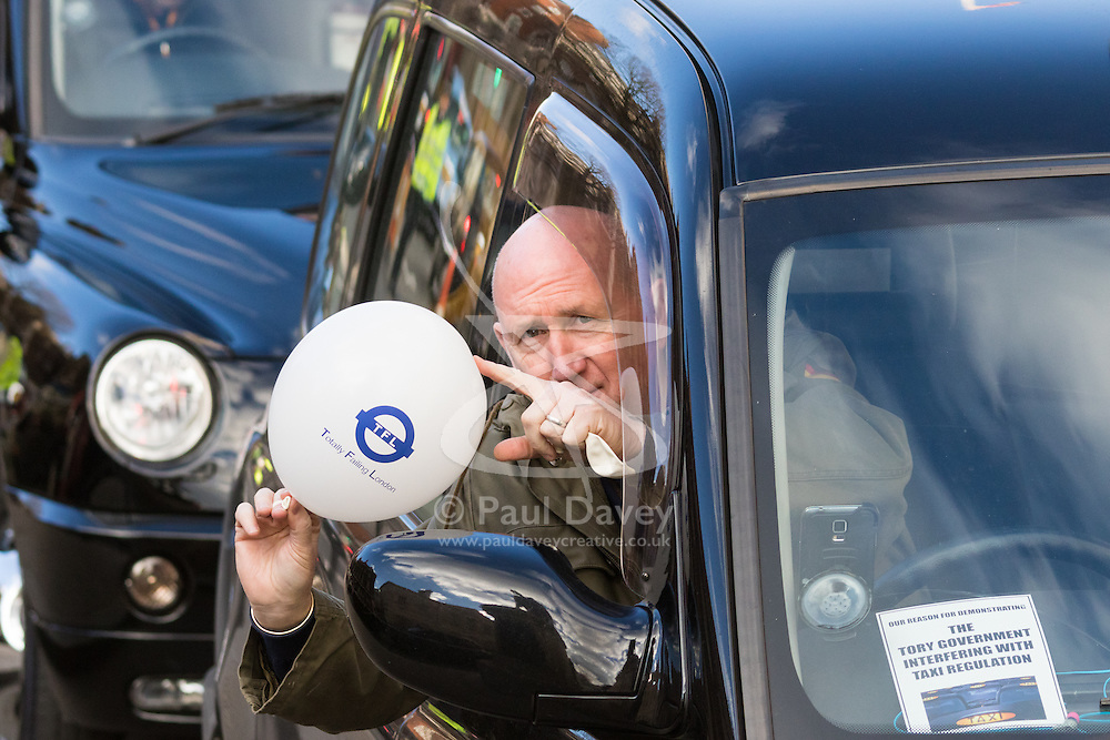 """Whitehall, London, February 10th 2016. A driver displays a white baloon emblazoned with """"TFL Totally Failing London"""" as an estimated 8,000 cabbies hold a go-slow in protest against what they say is unfair competition from minicab and Uber drivers who do not have to undergo the rigorous training and checks required for the licenced taxi trade. ///FOR LICENCING CONTACT: paul@pauldaveycreative.co.uk TEL:+44 (0) 7966 016 296 or +44 (0) 20 8969 6875. ©2015 Paul R Davey. All rights reserved."""