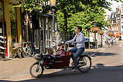 In Utrecht fietst een moeder met twee kinderen op een bakfiets door de historische binnenstad.<br /> <br /> In Utrecht a young mother is cycling with two children on a cargo bike at the historical center.