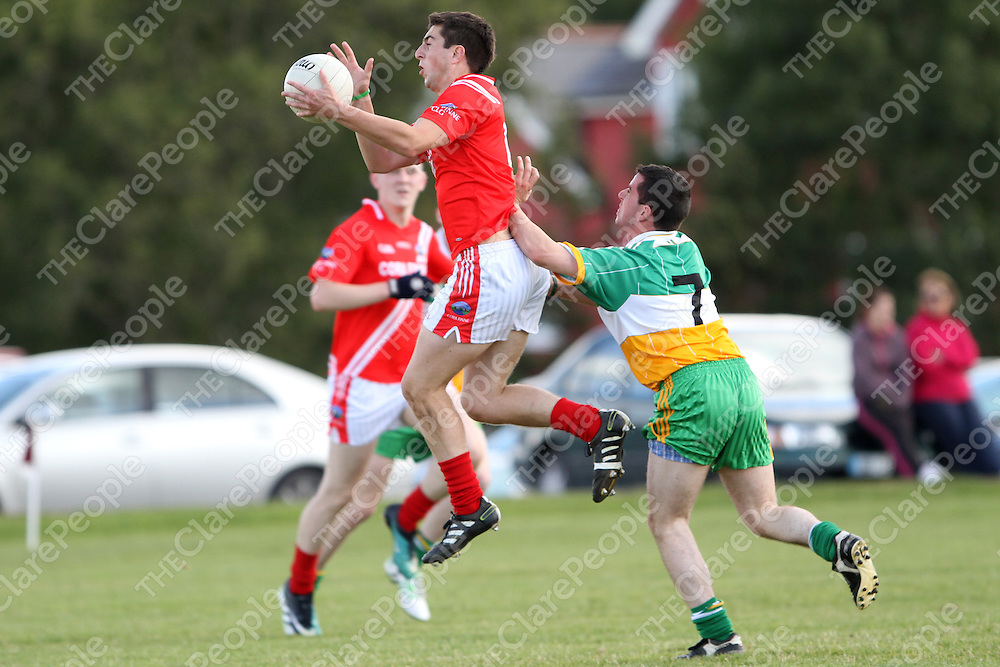 Corofin's Darren Malone collects possession ahead of Kidysart/Coolmeen's Martin McMahon during their U21B Semi Final at Gurteen. - Photograph by Flann Howard