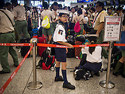 14 AUGUST 2013 - HONG KONG: A Hong Kong Sea Scout waits with a group of Sea and Boy Scouts to board a delayed flight at Hong Kong International Airport. Dozens of flights were delayed at one of the busiest airports in Asia and Hong Kong raised their alert to level 8, the highest, and closed schools and many businesses because of Severe Typhoon Utor. The storm passed within 260 kilometers of Hong Kong before making landfall in mainland China. Severe Typhoon Utor (known in the Philippines as Typhoon Labuyo) is an active tropical cyclone located over the South China Sea. The eleventh named storm and second typhoon of the 2013 typhoon season, Utor formed from a tropical depression on August 8. The depression was upgraded to Tropical Storm Utor the following day, and to typhoon intensity just a few hours afterwards. The Philippines, which bore the brunt of the storm, reported 1 dead in a mudslide and 23 fishermen missing at sea.   PHOTO BY JACK KURTZ