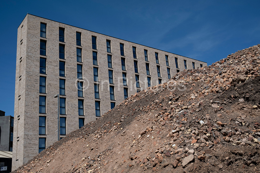 Huge pile of bricks as part of a development / redevelopment of old industrial builindgs in the city centre as new apartment buildings rise on 20th May 2020 in Birmingham, United Kingdom. The city is under a long term and major redevelopment, with much of its industrial past being demolished and made into new flats for residential homes.