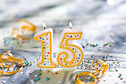 Fifteen (15)year celebration candle on U.S. currency.