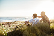 Father and son watching the surf and waves breaking at St Ouen's Bay, Jersey whilst sitting in the grassy sand dunes