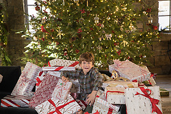 little boy surrounded by Christmas presents
