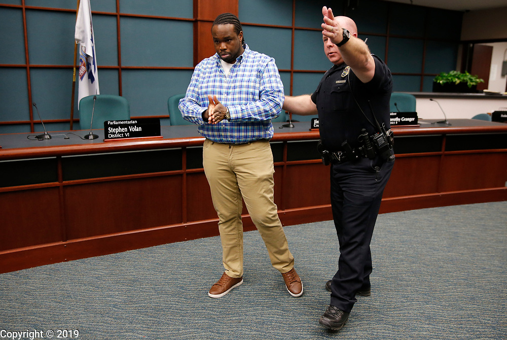 Bloomington Police Department Capt. Scott Oldham escorts Vauhxx  Booker, of Bloomington Black Lives Matter, from the council chambers after he interrupted a Bloomington City Council meeting to talk about the city's purchase of an armored personnel carrier for the Bloomington Police Department, Wednesday, April 11, 2018 in Bloomington, Ind.