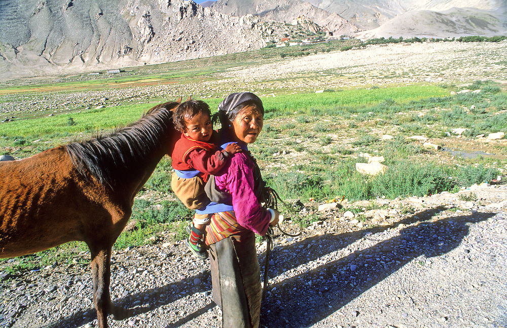 An elderly Tibetan woman carries a child and leads a horse towards a village in the distance in the Tibetan countryside.